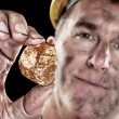 Gold miner with nugget — Stock Photo