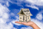 Money house held against the sky — Stock Photo