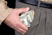 Man stuffing wads of cash into his pocket — Stock Photo