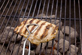 Barbecued chicken breast on barbecue — Stock Photo