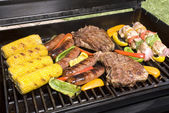 Barbecued steaks, brats, corn and chicken — Stock Photo