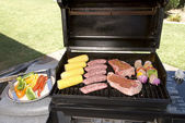 Barbecue with steaks, brats chicken and corn — Stock Photo