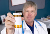 Doctor holding pill bottle — Stock Photo