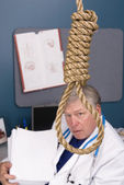 Doctor, noose and pile of paperwork — Stock Photo