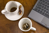 Coffee mugs and stress with laptop — Stock Photo