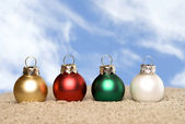 Christmas ornaments on the beach — Stock Photo