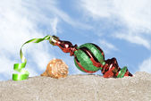 Christmas ornament on beach — Stock Photo