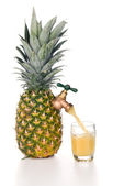 Pineapple juice pouring into glass — Stock Photo