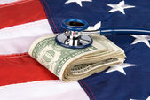 American flag with pile of cash and stethoscope — Stock Photo