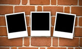 Brick wall with photographs — Stock Photo