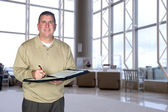Businessman taking notes in lobby — Stock Photo