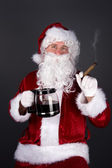 Santa Claus smoking a cigar and drinking coffee — Stock Photo