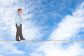 Businessman walking on tightrope — Stock Photo