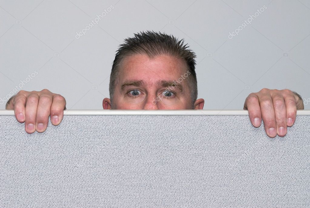 A male office worker peers over a cubicle because he is nosey. — Stock Photo #7636949