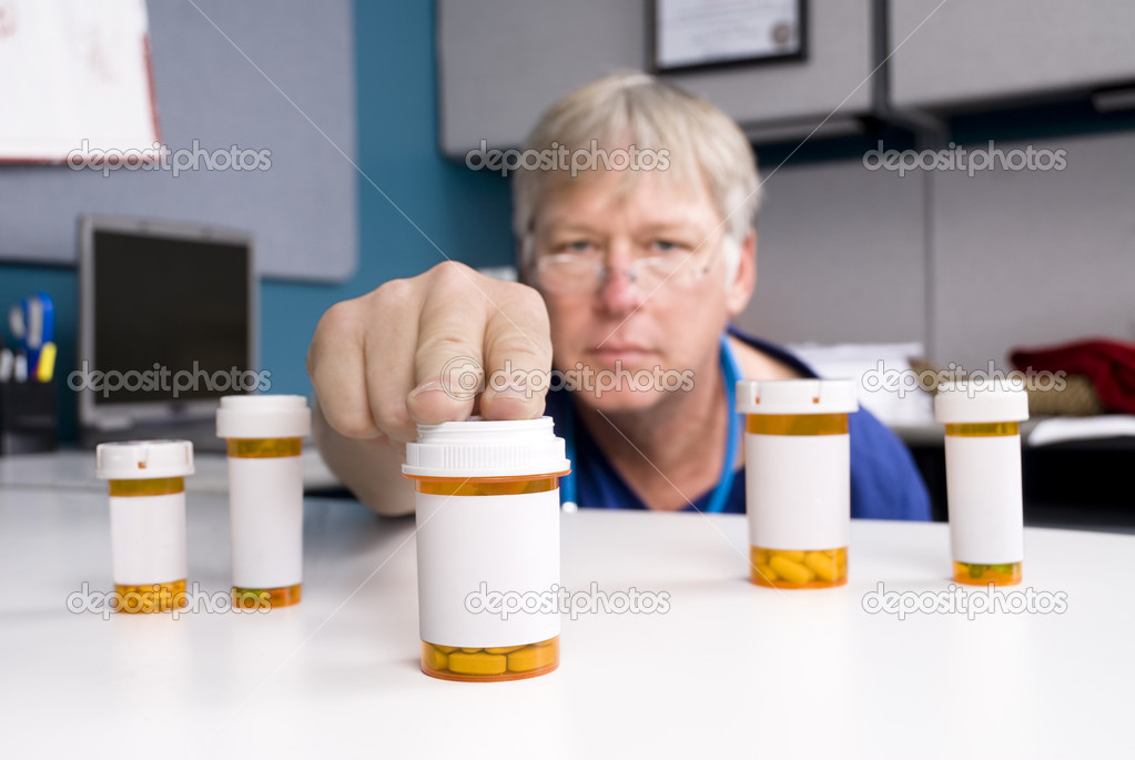A pharmacist selects the right medication for his patient.  Labels are blank to allow for copy to be placed on the pill bottles. — Stock Photo #7637812