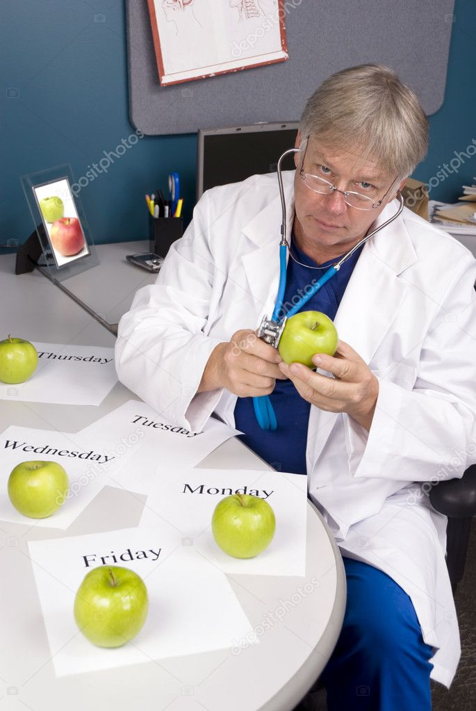 A doctor examines an apple with his stethoscope.  Image is useful for any healthy diet or eating inference. — Stock Photo #7637816