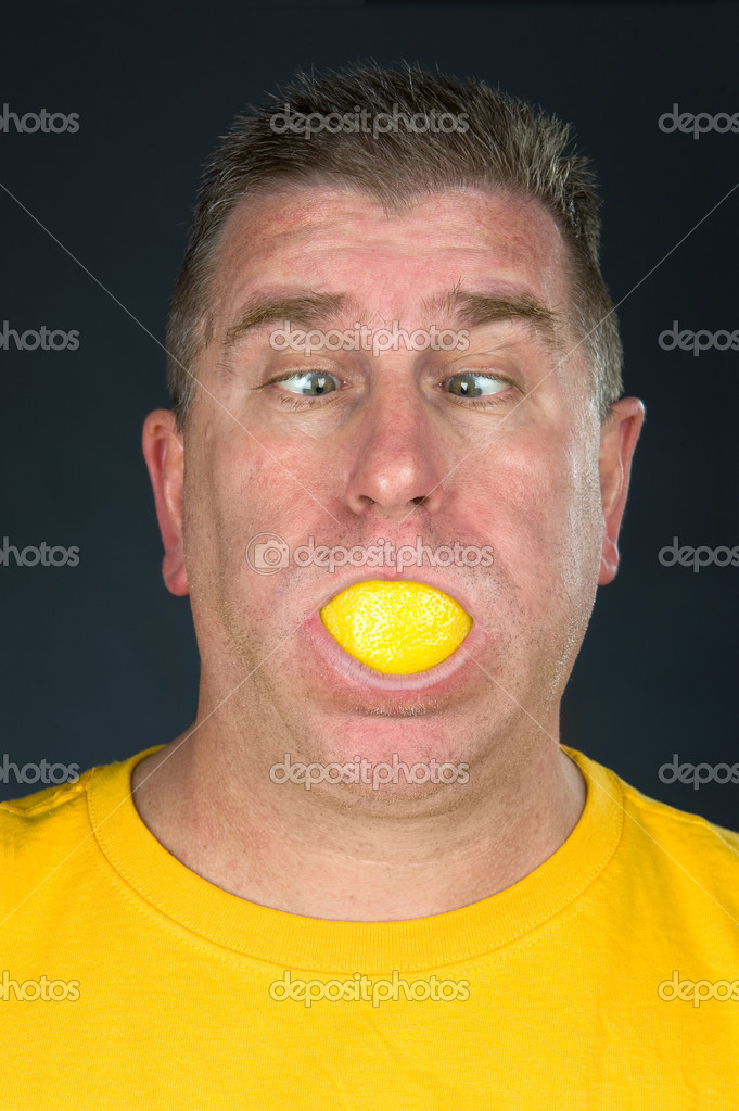 A man sucks on a very sour lemon slice and makes a funny face due to the tart flavor. — Stock Photo #7638259