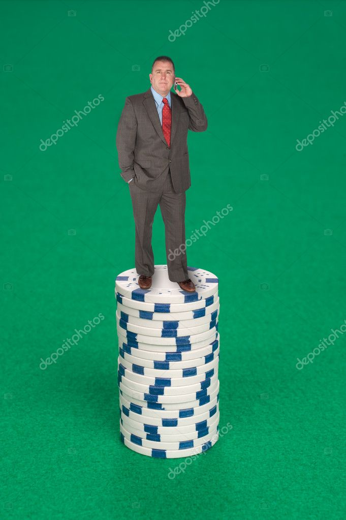 A man stands on a stack of poker chips calling in his bet. — Stock Photo #7638282