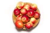 Red apples in a wooden plate — Stock Photo