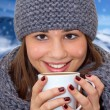 Portrait of young woman holding hot beverage - Lizenzfreies Foto
