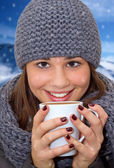 Portrait of young woman holding hot beverage — Stockfoto