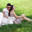 Young man with laptop and girl on green grass — Stock Photo