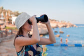 Female with a telescope at the seashore — Stock Photo