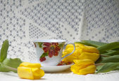 White cup with red tulip drawing standing on a saucer and yellow — Stock Photo