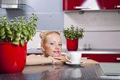 コーヒーを飲むの台所に座っている若い美しい女性 — ストック写真