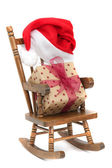 Old wooden rocking Chair with red jelly bag cap and christmas present — Stock Photo