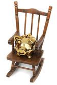 Old wooden rocking chair and golden piggy bank on white — Stock Photo