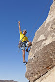 Male rock climber clings to a cliff. — Stockfoto
