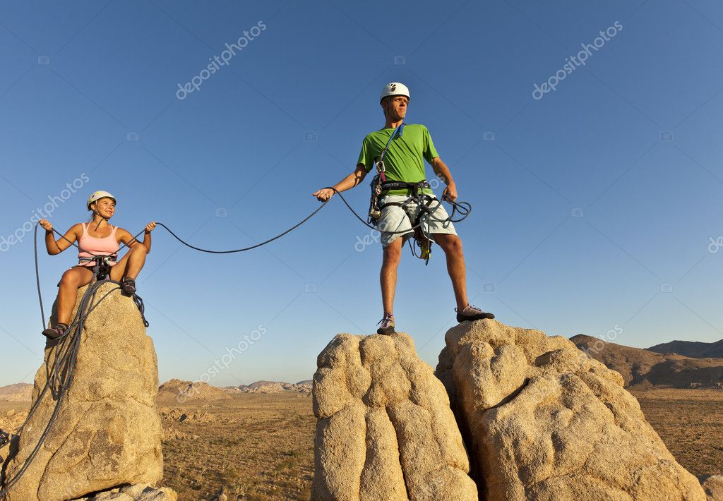 Team of rock climbers struggle to the summit of a challenging cliff.  Foto Stock #6881962