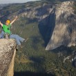 Rock climber celebrates on the summit. - Stock Photo