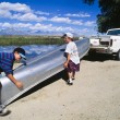 Boys loading canoe into truck. - Photo