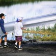 Boys loading canoe into truck. - Stock Photo