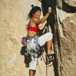 Stok fotoğraf: Rock climber clinging to a cliff.