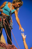 Climber reaching for a helping-hand. — Stock Photo