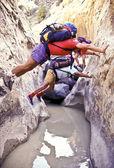 Hikers navigate a slot canyon. — Stock Photo
