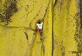 Male climber working his way up a steep crack. — Stockfoto