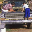 Father and son fixing truck. - Stock Photo