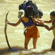 Female climbing team fording river. - Stock Photo