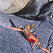 Female climber clinging to the edge. — Stock Photo