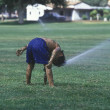 Boy playing in sprinklers. - Stock Photo