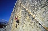 Female climber clinging to the edge. — Stock Photo
