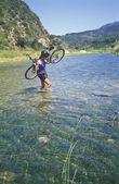 Female mountain biker carrying bike. — Stock Photo