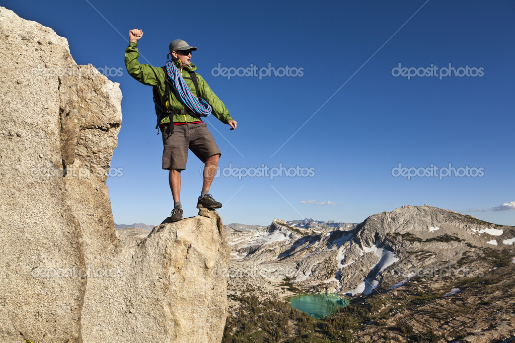 Male rock climber celebrates on the summit after a successful ascent. — Stock Photo #7384508