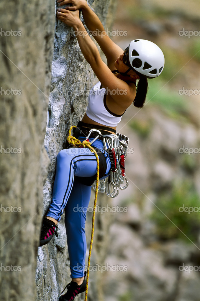 Female rock climber is focused on her next move as she battles her way up a steep cliff in the Owens River Gorge, California. — Stock Photo #7385511