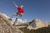 Climber rappelling from the summit. — Stock Photo