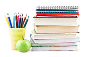 Coloured pencils in jar with textbooks and apple — Stock Photo
